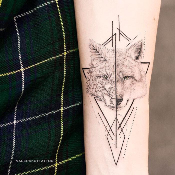 Женское тату на предплечье в стиле графика и дотворк. Татуировка с волком, цветами и геометрией