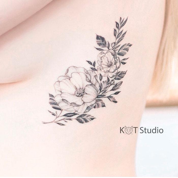 Татуировка с цветами на боку для девушек. Женское тату на ребрах в стиле графика и дотворк.