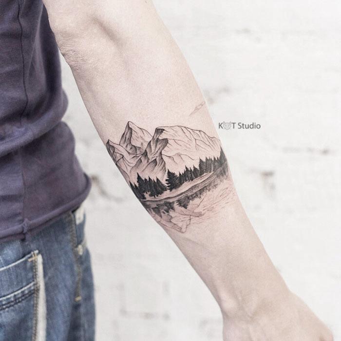 Мужское тату на предплечье в стиле графика и випшейдинг. Татуировка горы, лес и озеро. Отличная идея для мужского браслета