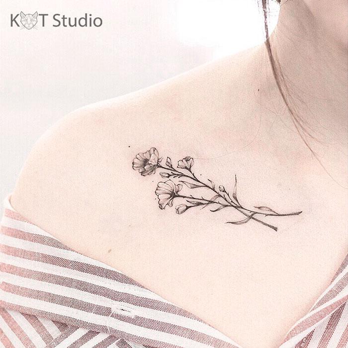 Женское тату с цветами на ключице. Татуировка для девушек в стиле дотворк и графика.