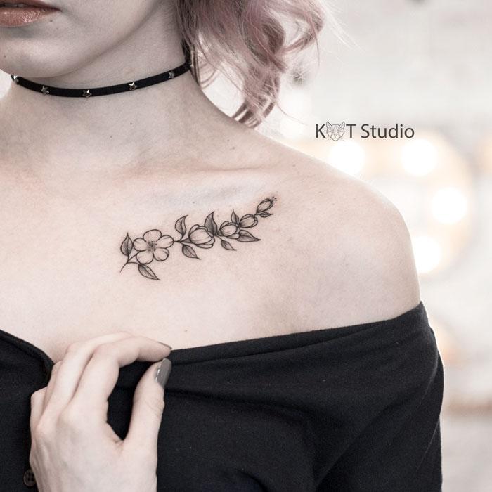 Женское тату на ключице в стиле графика и випшейдинг. Татуировка ветвь сакуры