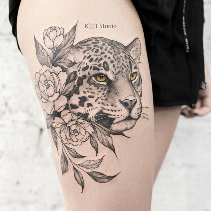 Женское тату на бедре в стиле графика и випшейдинг. Татуировка леопарда с пионами