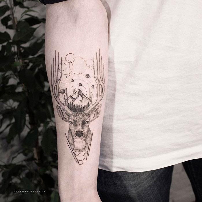 Мужское тату на предплечье в стиле графика и дотворк. Татуировка с оленем, космосом и горами