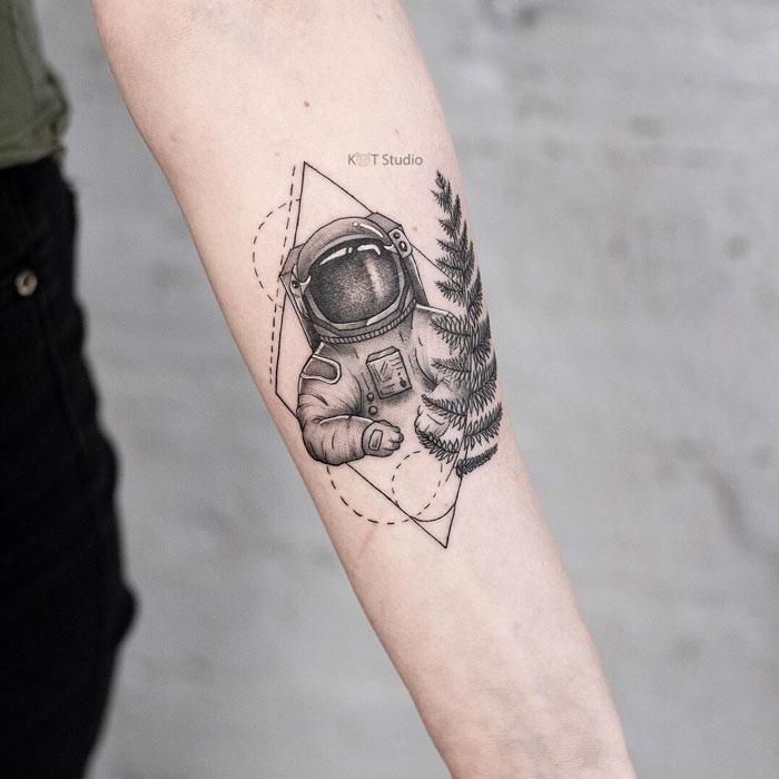 Женское тату на предплечье в стиле графика и випшейдинг. Татуировка космонавт, папоротник и геометрия