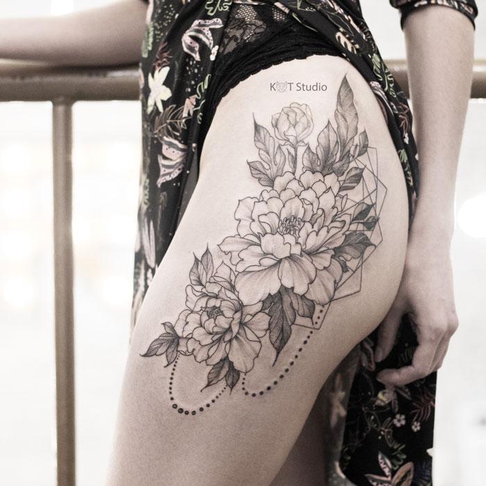 Женское тату на бедре в стиле графика и дотворк. Татуировка с цветами и элементами геометрии