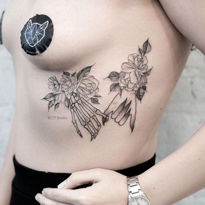Женское тату на ребрах в стиле графика и дотворк. Татуировка с пионами и руками скелета