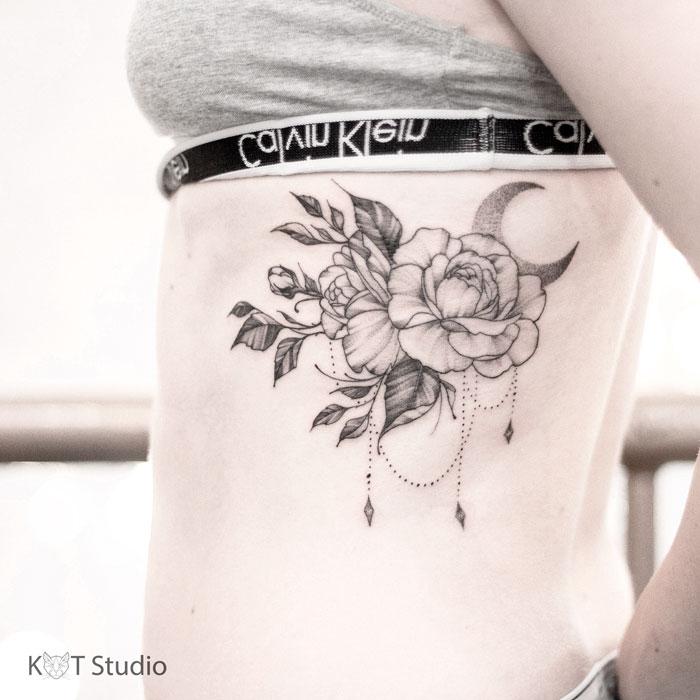 Женское тату с розой и месяцем на боку. Татуировка для девушек в стиле дотворк и графика под грудью.