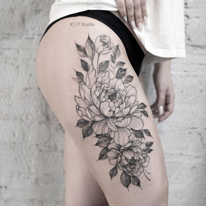 Женское тату на бедре в стиле графика и дотворк. Татуировка с пионами