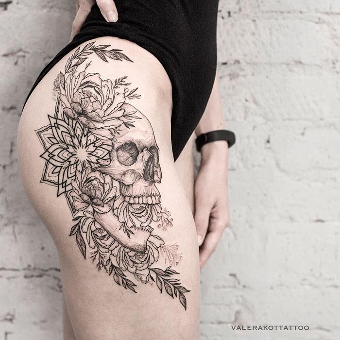 Женское тату на бедре в стиле графика и орнаментал. Татуировка с черепом, мандалой и пионами