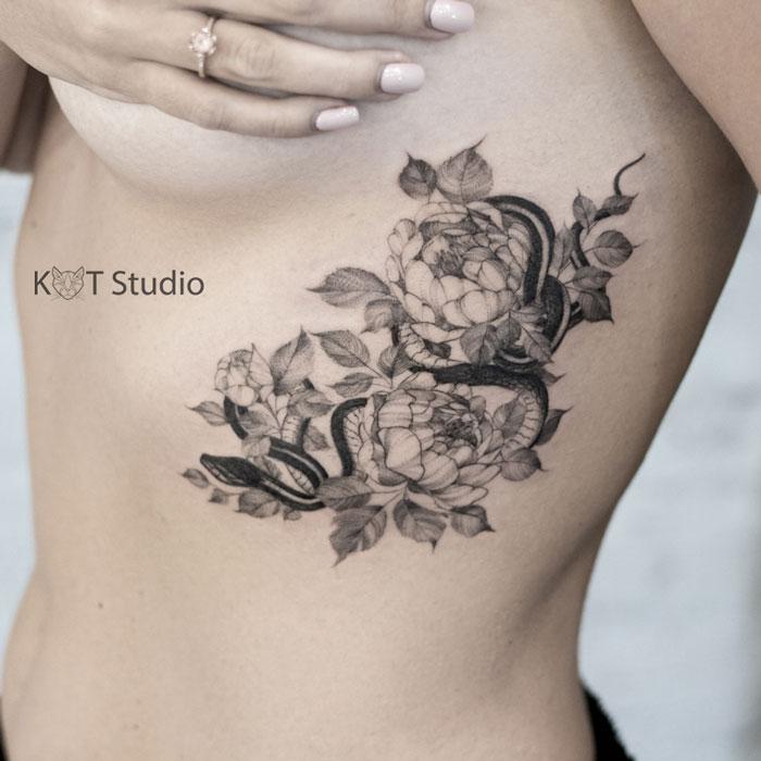 Татуировка с цветами и змеей на боку для девушек. Женское тату на ребрах в стиле графика и дотворк.