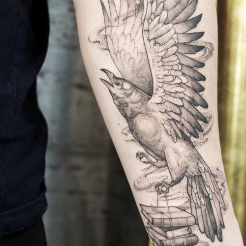 Женское тату на предплечье в стиле графика и дотворк. Татуировка с вороном и книгами