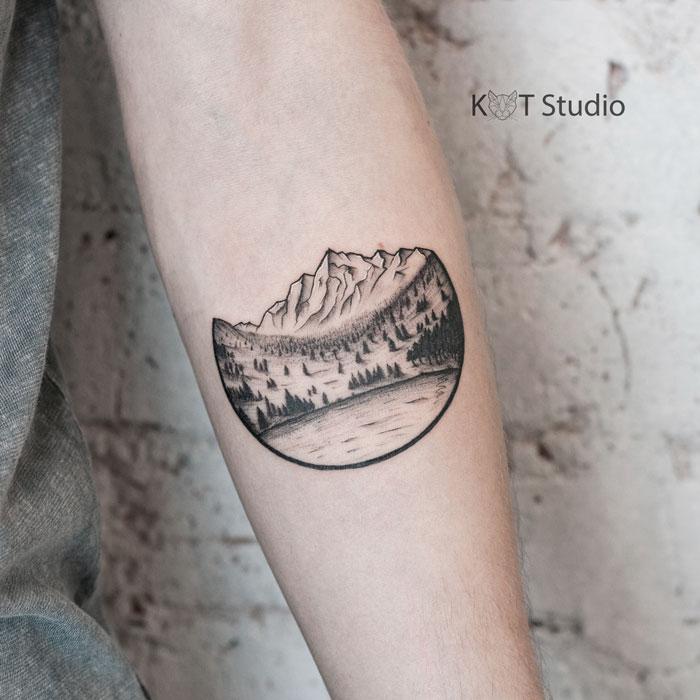 Женское тату на предплечье в стиле графика и випшейдинг. Татуировка горы, лес и озеро