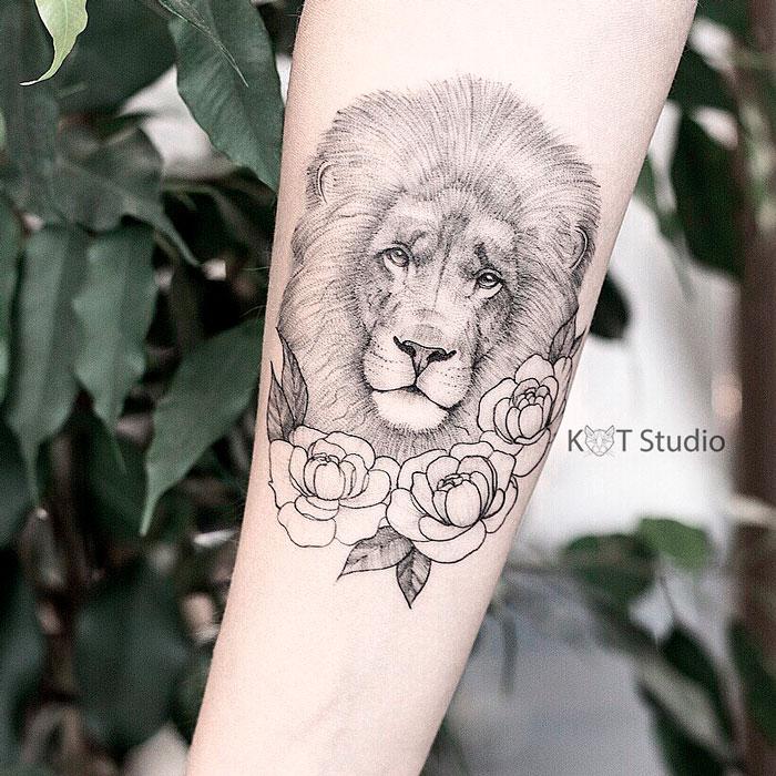 Женское тату на предплечье в стиле графика и випшейдинг. Татуировка лев с пионами