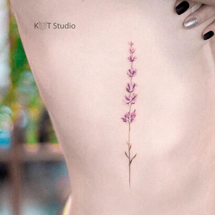 Татуировка лаванды на боку для девушек. Женское цветное тату на ребрах лиловых оттенков