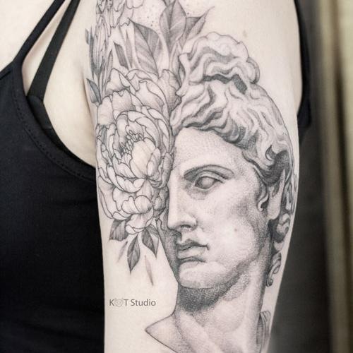 Женское тату в стиле графика и дотворк на плече. Татуировка с портретом Аполлона и пионами