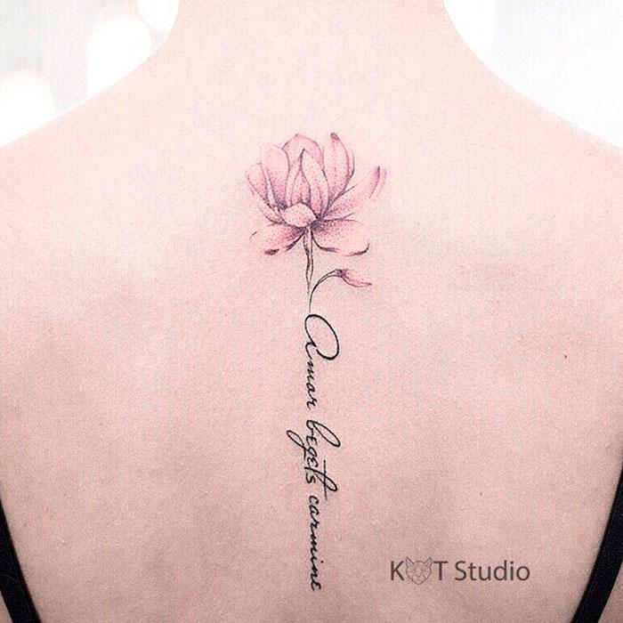 Татуировка с лотосом и надписью. Женское цветное тату на спине между лопаток в стиле графика.