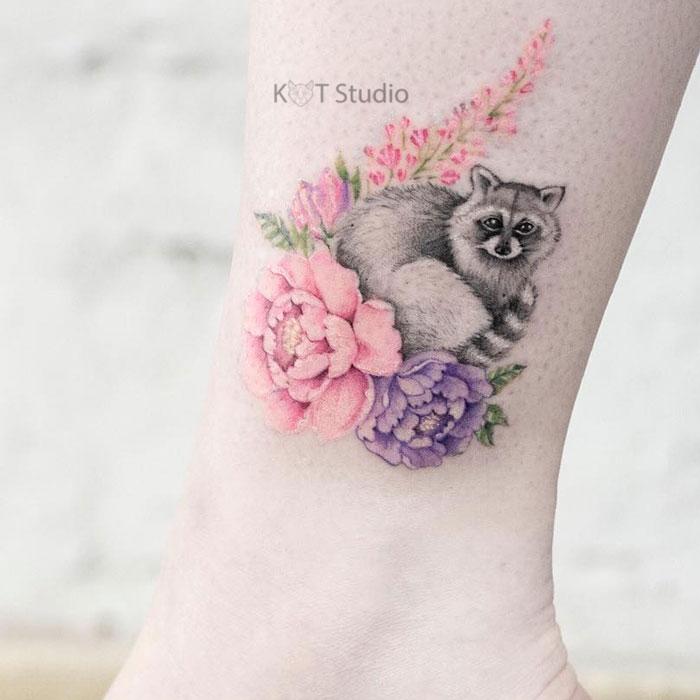 Женское цветное тату на икре. Татуировка с енотом и цветами на лодыжке