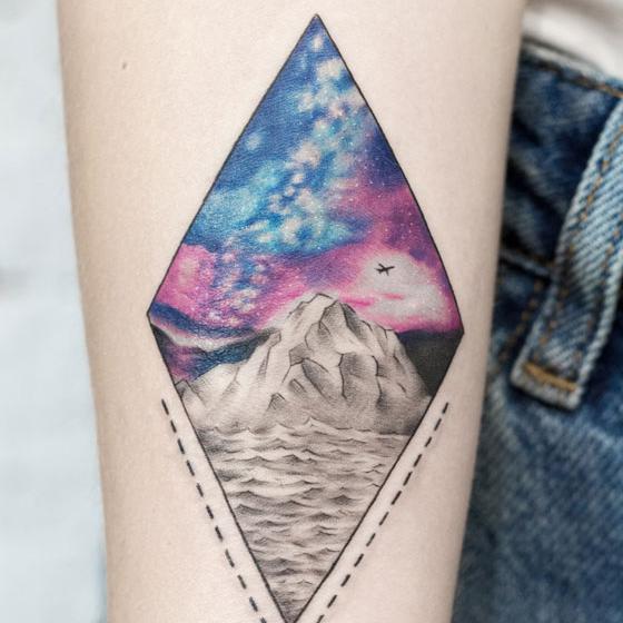 Женское цветное тату на предплечье. Татуировка с космосом, горами и морем