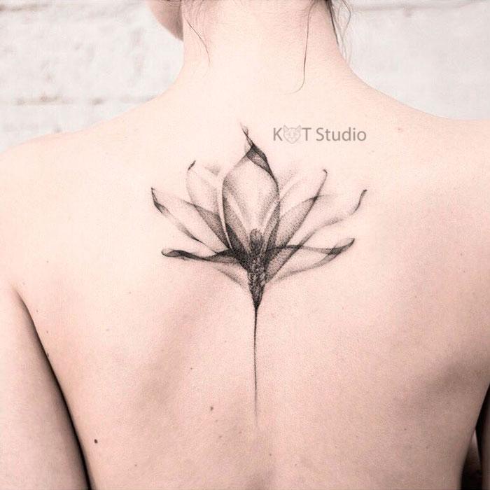 Татуировка лотос. Женское тату на спине между лопаток в стиле графика.