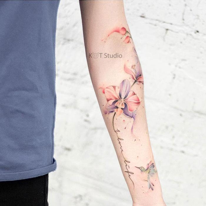 Цветное женское тату на руке с и орхидеями в стиле акварель и надпись. Татуировка на предплечье для девушек