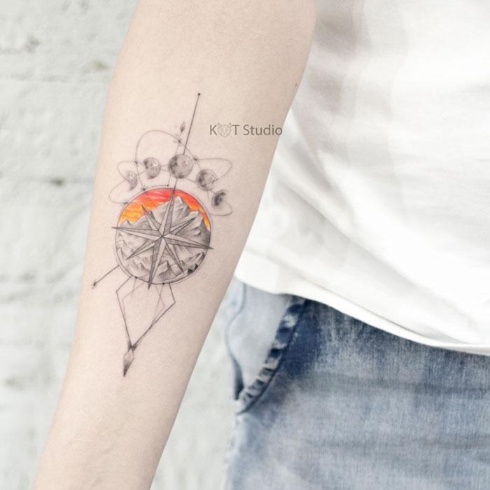 Женское тату на предплечье. Татуировка с компасом и горами