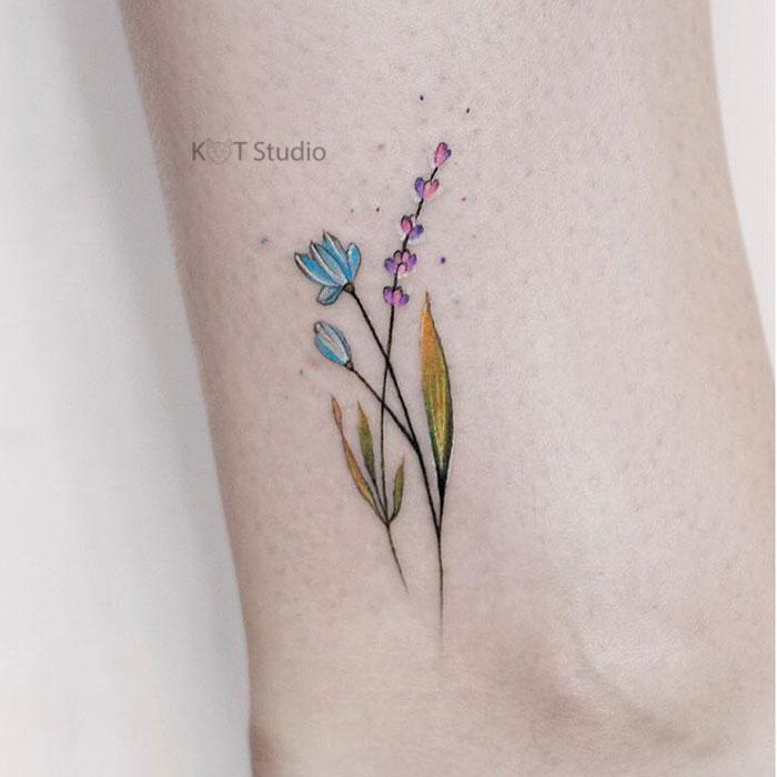 Маленькое цветное женское тату на ноге. Татуировка с цветами на икре