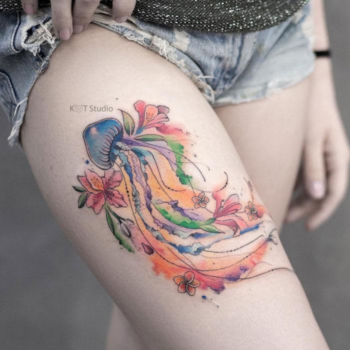 Цветное женское тату на ноге с медузой и орхидеями в стиле акварель. Татуировка на бедре для девушек