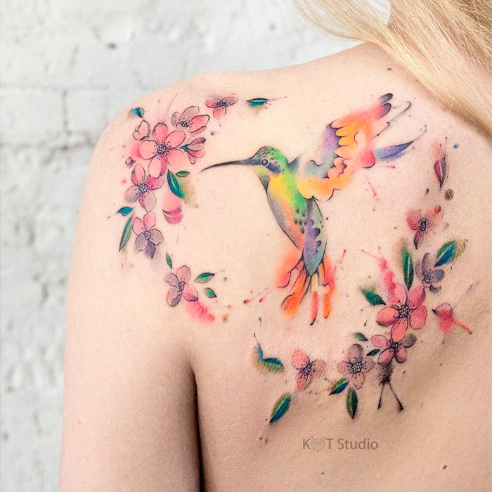 Женское цветное тату с птицей колибри и цветами сакуры на спине. Татуировка в на лопатке в стиле акварель для девушек