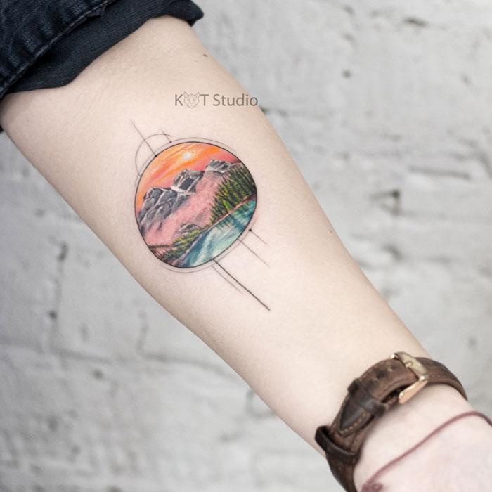 Женское цветное тату на предплечье с горами и лесом. Татуировка пейзаж с элементами геометрии