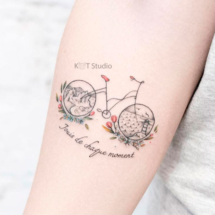 Маленькое женское цветное тату на предплечье. Татуировка с велосипедом и надписью для девушек