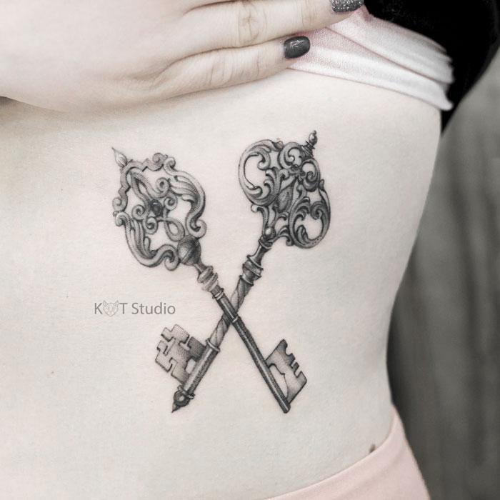 Женское тату на боку в стиле графика, дотворк и випшейдинг. Татуировка под грудью ключики