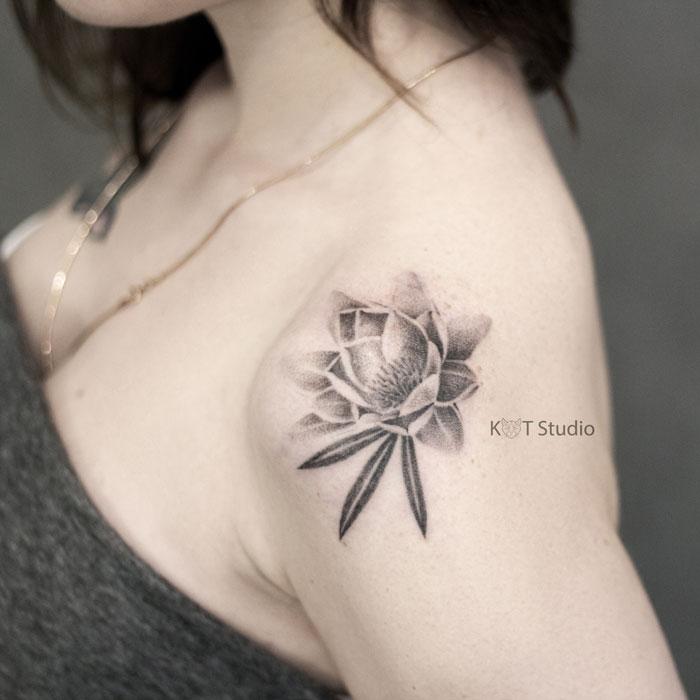 Татуировка с цветком лотоса для девушек на плече. Женское тату в стиле графика и дотворк