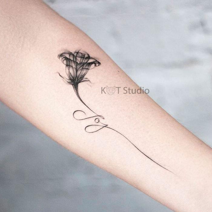 Женское тату на предплечье в стиле графика. Татуировка с колокольчиком и надписью