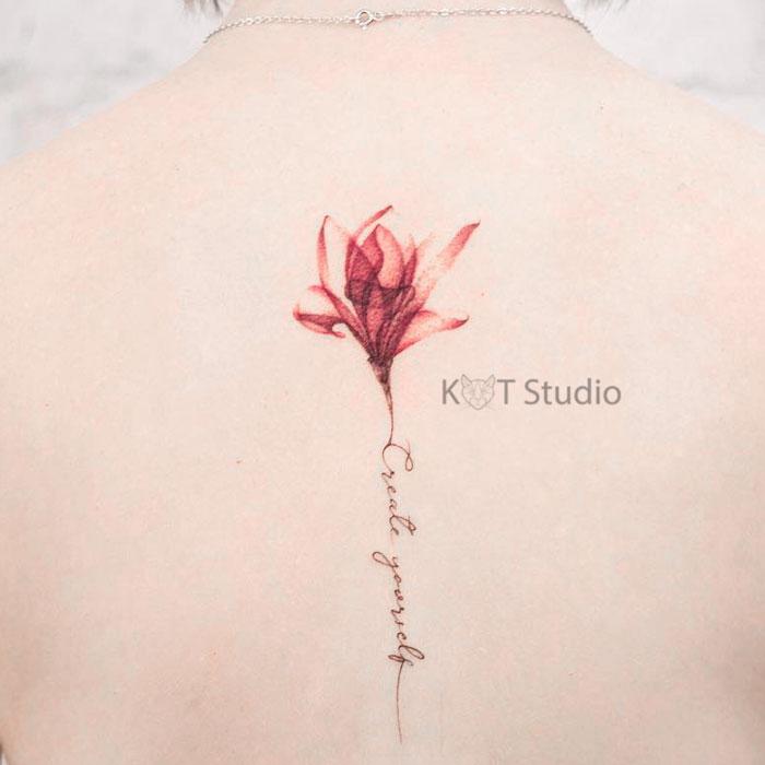 Тату цветок магнолия с тату надписью между лопаток. Женская цветная татуировка