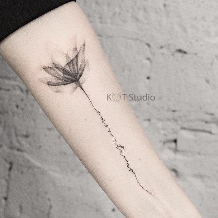 Тату цветок лотоса с тату надписью в стиле графика. Женская татуировка на предплечье