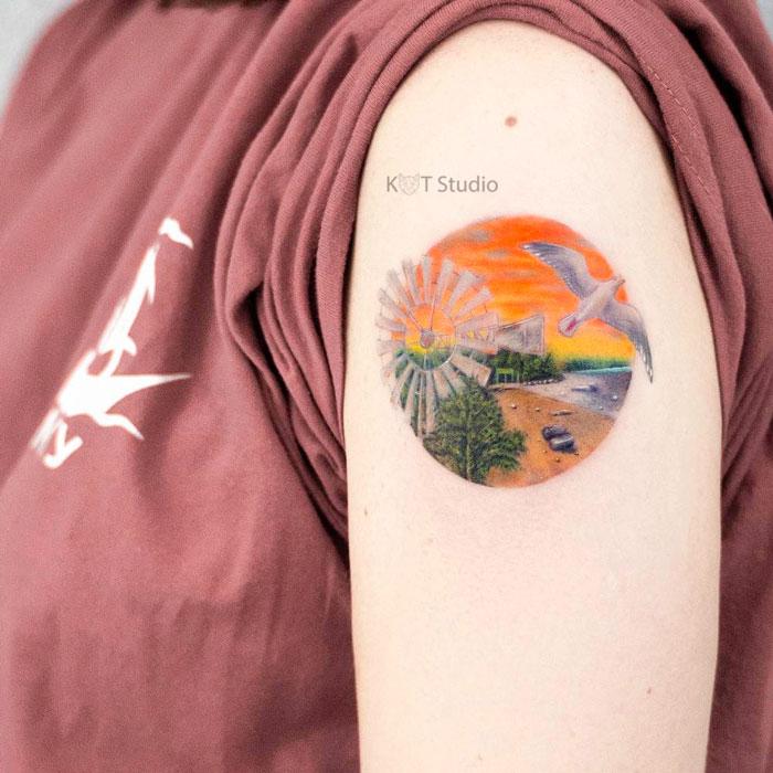 Женское цветное тату с птицей и мельницей. Татуировка на плече пейзаж