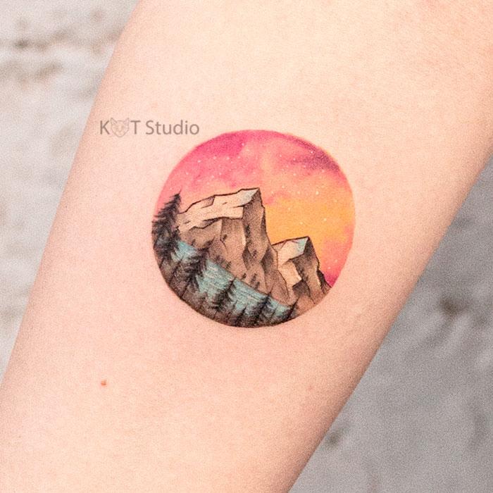 Женское цветное тату с горами и лесом. Татуировка пейзаж