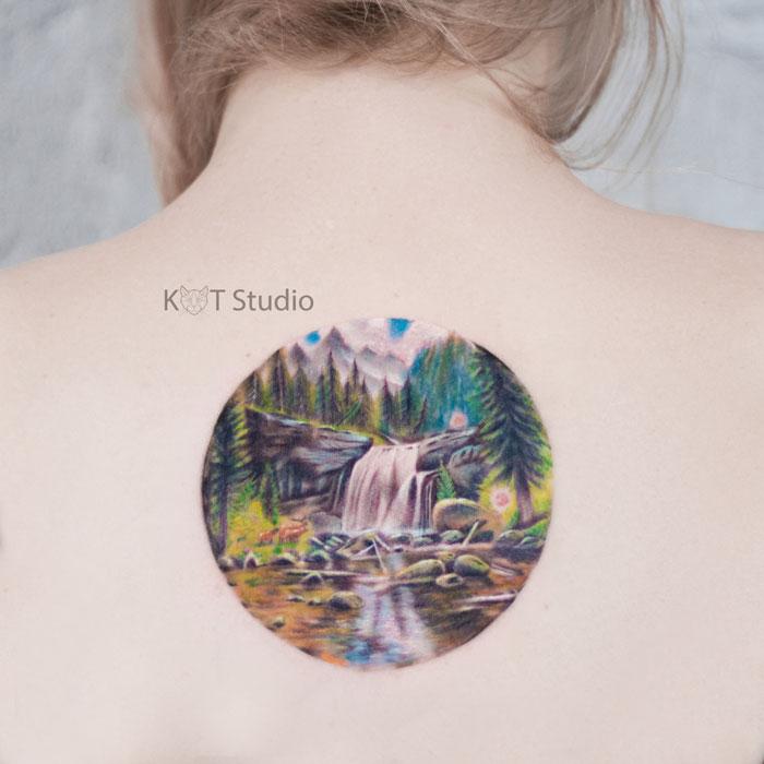 Женское цветное тату на спине. Татуировка между лопаток с лесом и водопадом