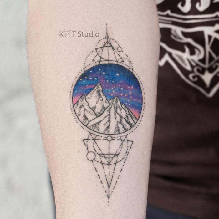Мужское тату на руке с горами, космосом и геометрией. Цветная татуировка на предплечье