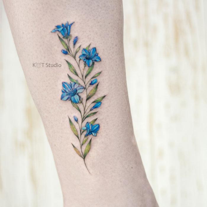 Женское цветное тату на ноге. Татуировка с колокольчиками на икре