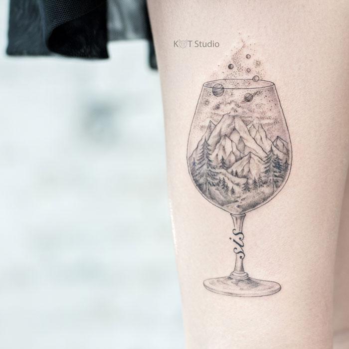 Женское тату на ноге в стиле графика и дотворк. татуировка с бокалом, горами и космосом на икре
