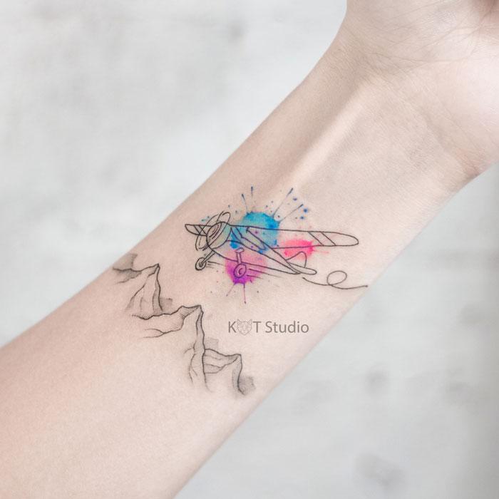 Женское небольшое тату на запястье в стиле акварель. Татуировка самолет и горы на предплечье для девушек.