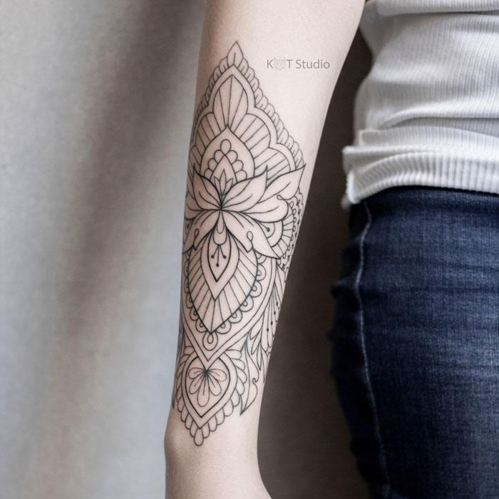 Женское тату лотос в стиле орнаментал на предплечье. Татуировка для девушек на предпелчье