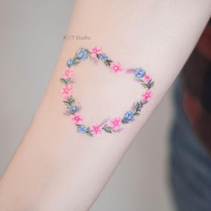 Женское маленькое тату сердце с цветами на предплечье. Татуировка для девушек цветная