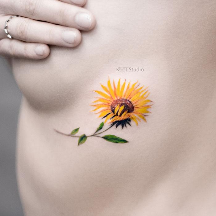 Женское тату на ребрах. Маленькая цветная татуировка подсолнуха под грудью для девушек