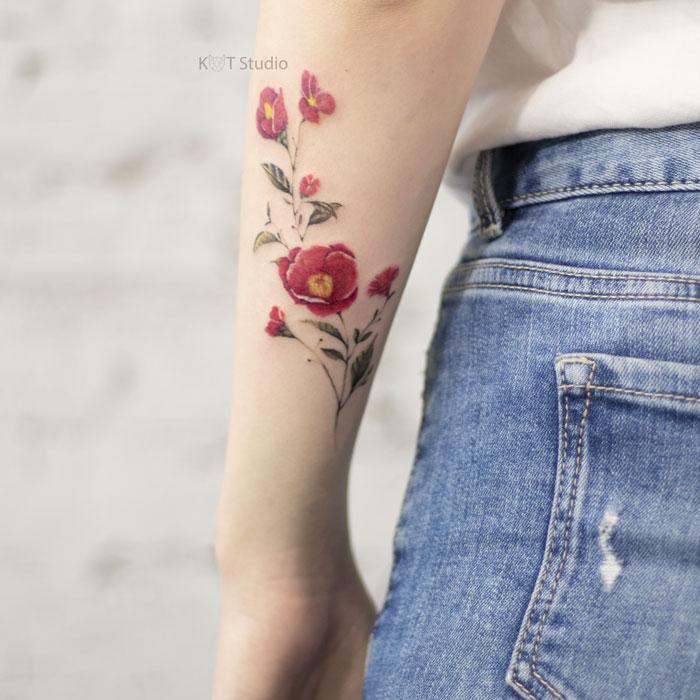 Женское цветное тату с цветами на предплечье. Татуировка на руку девушке